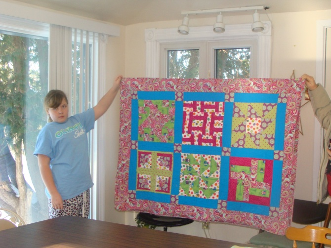 Our 11-year-old beginner quilter with her finished quilt!